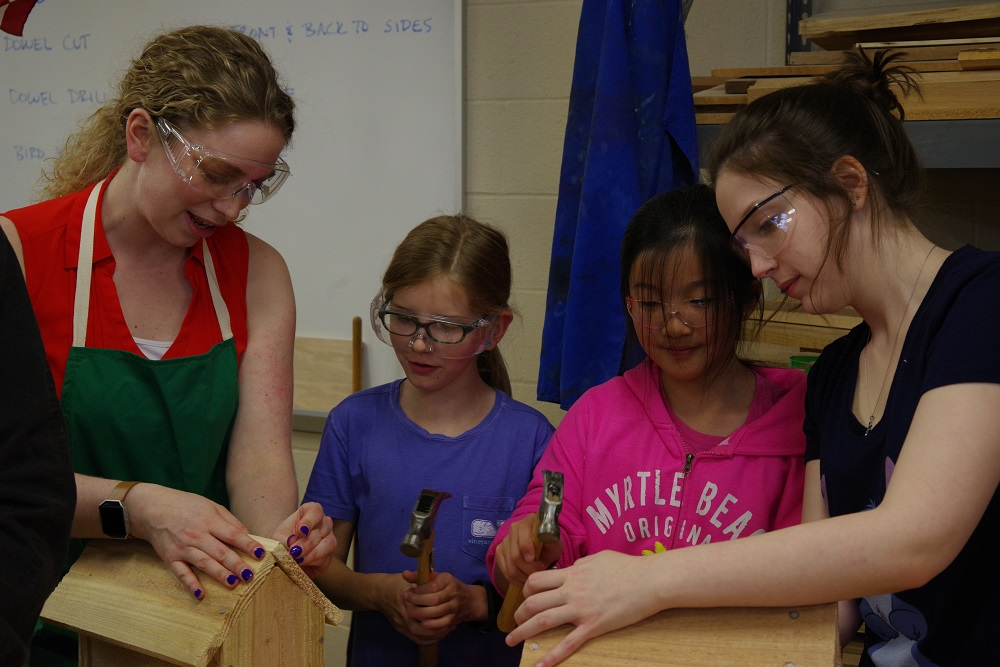 Bassett elementary teacher Leah Burke and WHS student Dori Hauser help Julia Richards and Natalie Chang with nailing.
